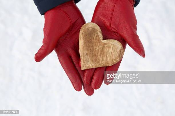 Cropped Image Of Hands With Leather Gloves Holding Wooden Heart Over Snow