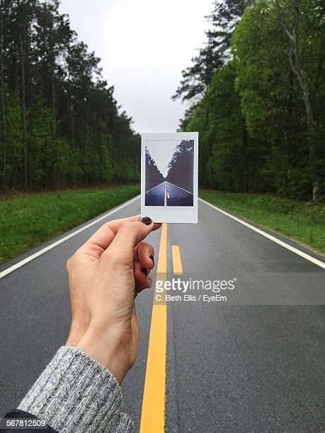 Cropped Image Of Holding Photograph On Road Against Clear Sky
