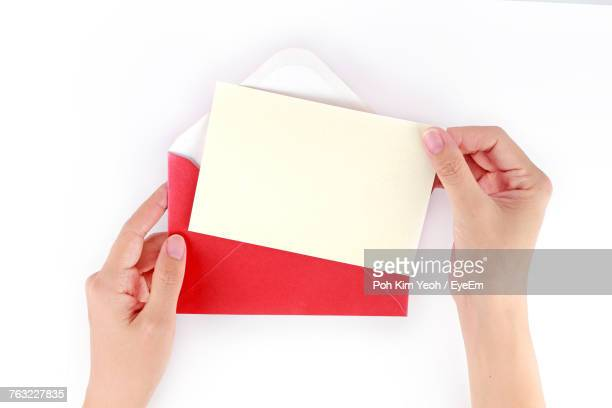 cropped image of human hand holding envelope against white background - bericht stockfoto's en -beelden
