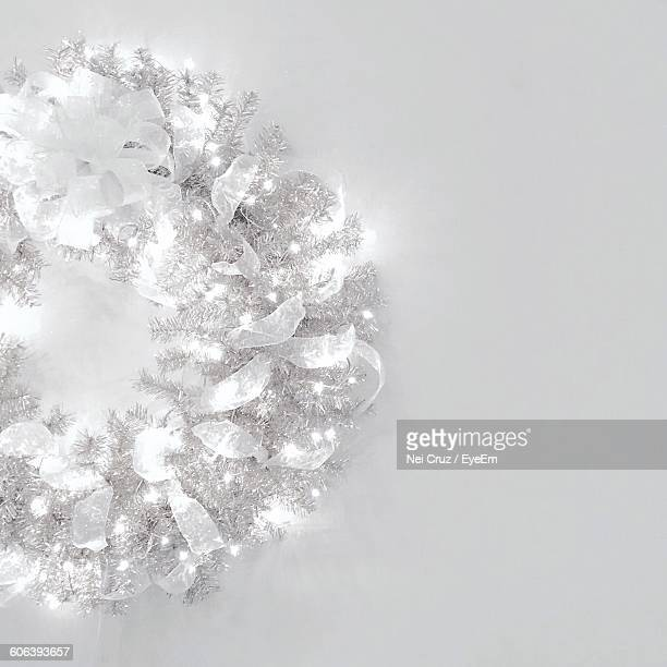 Cropped Image Of Illuminated Wreath Over White Wall