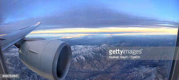 cropped image of jet engine over rocky mountains against sky - aircraft wing stock pictures, royalty-free photos & images