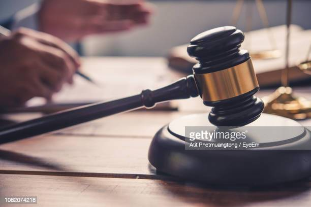 cropped image of judge working with gavel in foreground - judge law stock pictures, royalty-free photos & images