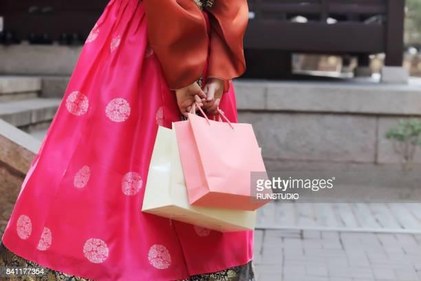 cropped image of  korean woman wearing hanbok holding shopping bags - bolsa rosa - fotografias e filmes do acervo