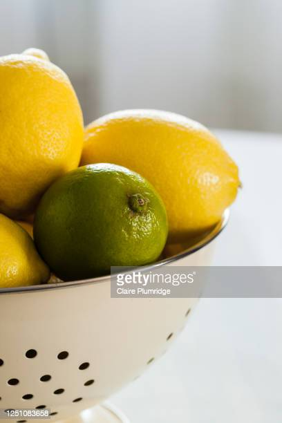 cropped image of lemons and limes in a colander on a wooden table with a light background - newbury england stock pictures, royalty-free photos & images