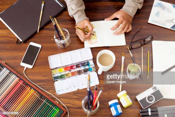 cropped image of male illustrator making painting at desk in creative office - illustrator stock photos and pictures