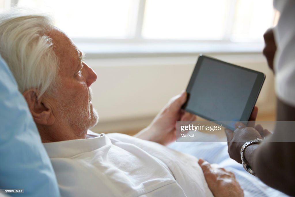 Cropped image of male nurse assisting senior man in using digital tablet at hospital : Stock Photo