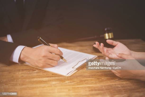 cropped image of man and woman on table - legal trial stock pictures, royalty-free photos & images