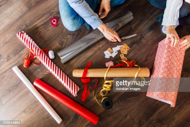 cropped image of man and woman wrapping gifts at home - gift wrapping stock pictures, royalty-free photos & images
