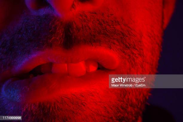 cropped image of man biting lips in darkroom - biting lip stock pictures, royalty-free photos & images