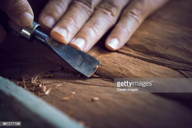 cropped image of man carving in workshop - handgemacht stock-fotos und bilder
