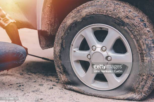 cropped image of man changing flat tire - flat tire stock pictures, royalty-free photos & images