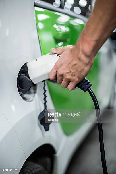 Cropped image of man charging electric car at gas station