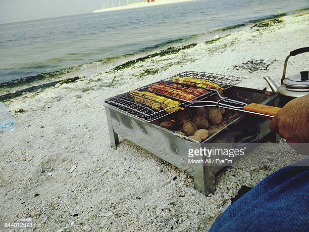 Cropped Image Of Man Cooking Food On Barbecue Grill At Beach