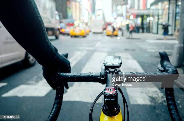 cropped image of man cycling on road in city during rainy season - handlebar stock photos and pictures