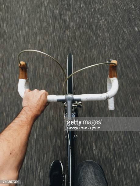 cropped image of man cycling on street - handle stock pictures, royalty-free photos & images