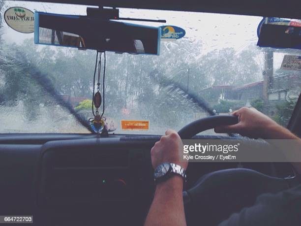 Cropped Image Of Man Driving Car During Monsoon