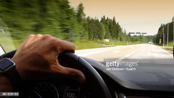 Cropped Image Of Man Driving Car On Road
