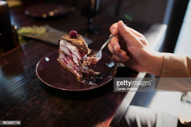 Cropped image of man eating cake slice at table