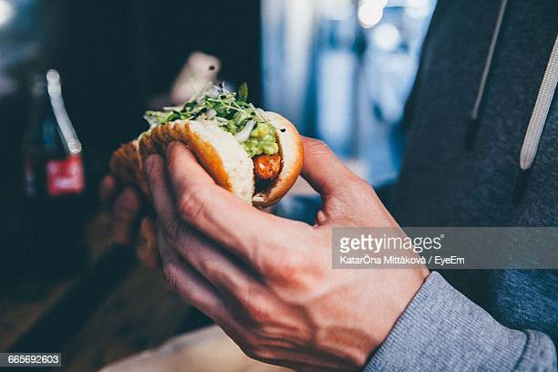 Cropped Image Of Man Eating Hot Dog
