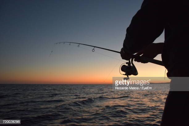Cropped Image Of Man Fishing At Sea Against Clear Sky During Dusk