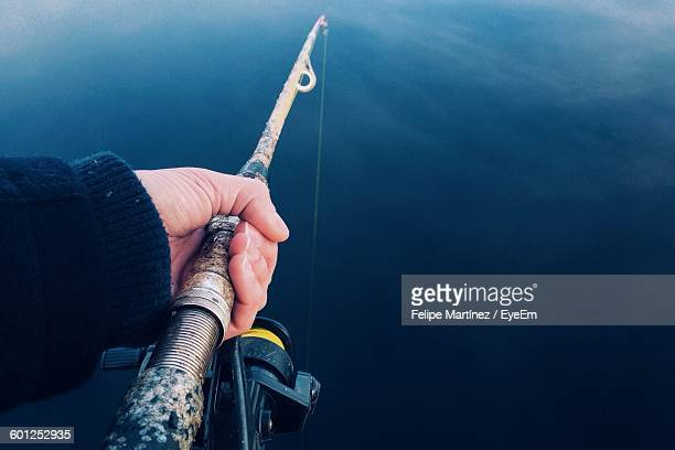 cropped image of man fishing in lake - unusual angle stock pictures, royalty-free photos & images