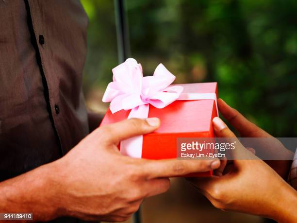 Cropped Image Of Man Giving Gift To Woman