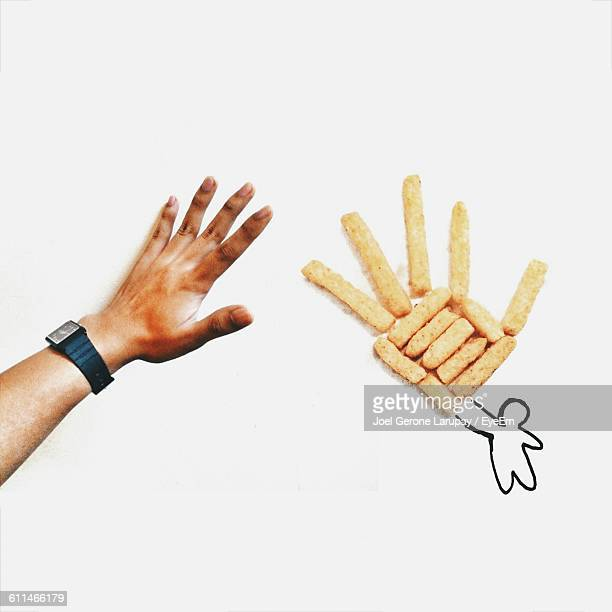 Cropped Image Of Man Giving High-Five To Doodle Hand With French Fries