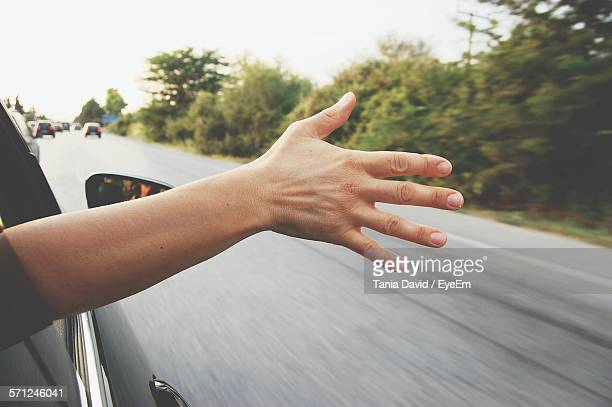 Cropped Image Of Man Hand Coming Out From Car Window Against Clear Sky