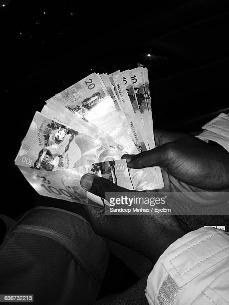 cropped image of man hand holding canadian currency - canadian one hundred dollar bill stock pictures, royalty-free photos & images