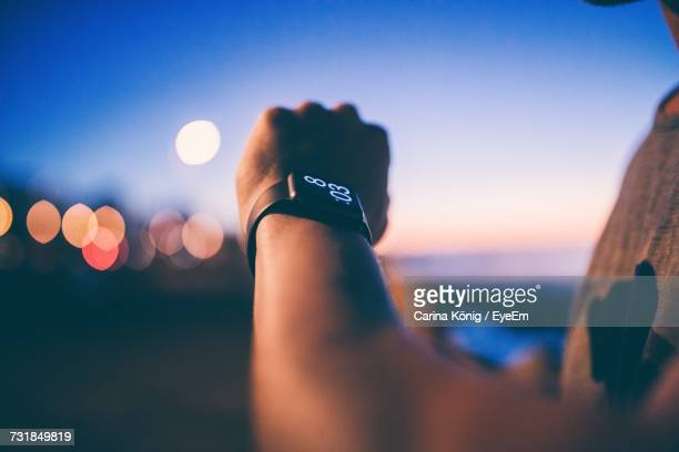 cropped image of man hand wearing smart watch against sky during sunset - wrist watch stock pictures, royalty-free photos & images