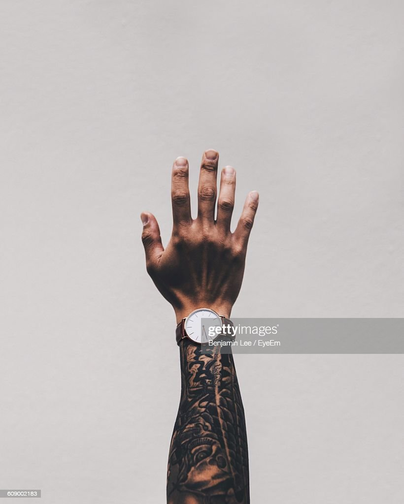 Cropped Image Of Man Hand With Tattoo Wearing Wrist Watch Against White Background : Stock-Foto