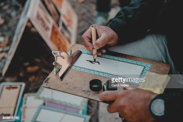 cropped image of man hand writting a name in arabic caligraphy in the street Granada,Spain