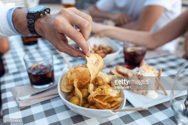 cropped image of man having potato chip at cafe - alcohol stock pictures, royalty-free photos & images