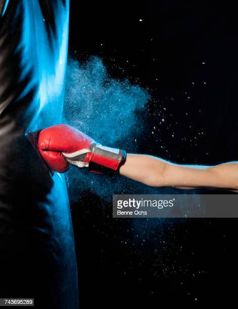 cropped image of man hitting punching bag against black background - 殴る ストックフォトと画像