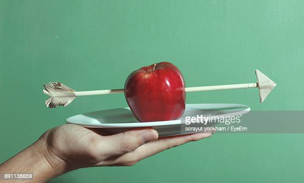 Cropped Image Of Man Holding Apple With Arrow On Plate Against Green Background