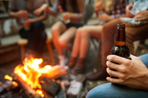 Cropped image of man holding beer bottle while camping with friends - gettyimageskorea