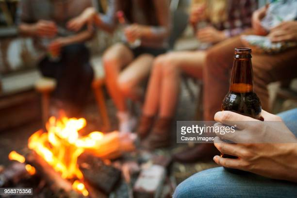 cropped image of man holding beer bottle while camping with friends - bonfire stock pictures, royalty-free photos & images