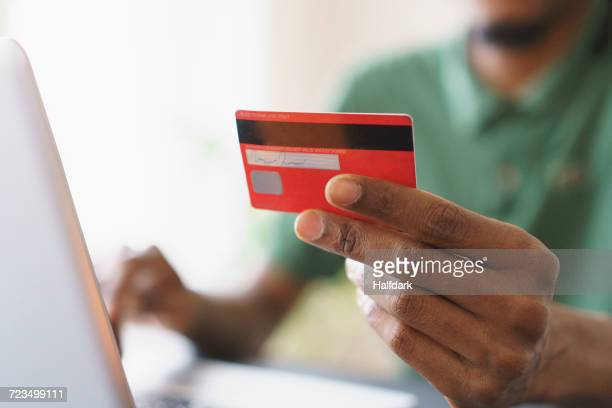 cropped image of man holding credit while shopping online through laptop at home - spending money stock pictures, royalty-free photos & images