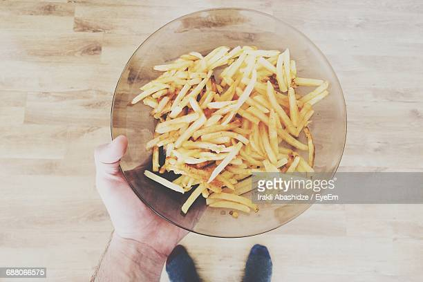 Cropped Image Of Man Holding French Fries In Bowl