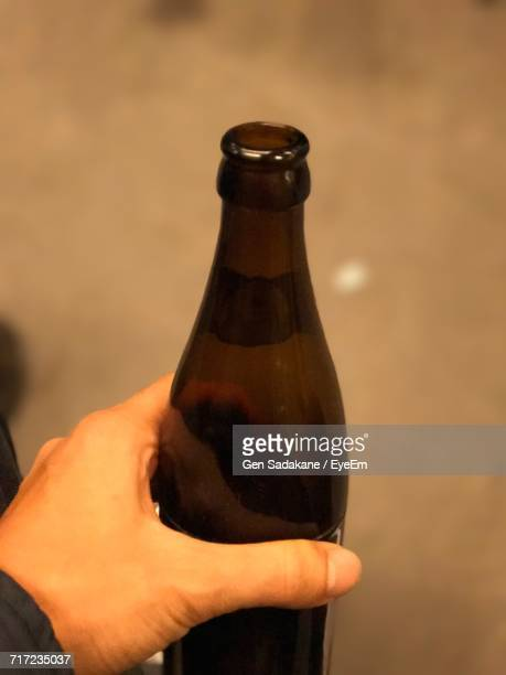 Cropped Image Of Man Holding Glass Bottle