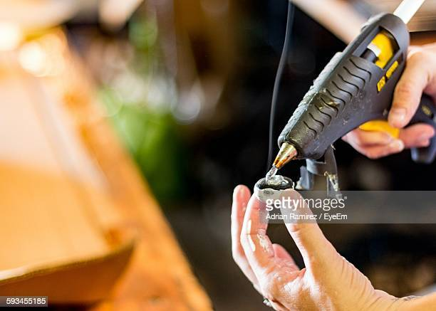 Cropped Image Of Man Holding Glue Gun At Workshop