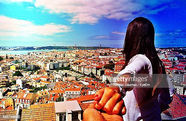 Cropped Image Of Man Holding Hand Of Woman Against Sky In City