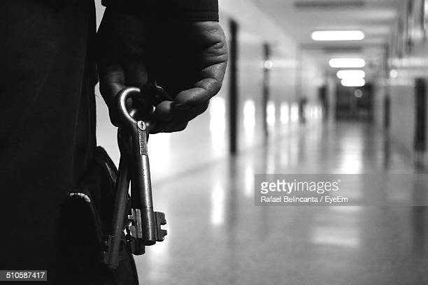cropped image of man holding keys in corridor - prison guard stock pictures, royalty-free photos & images