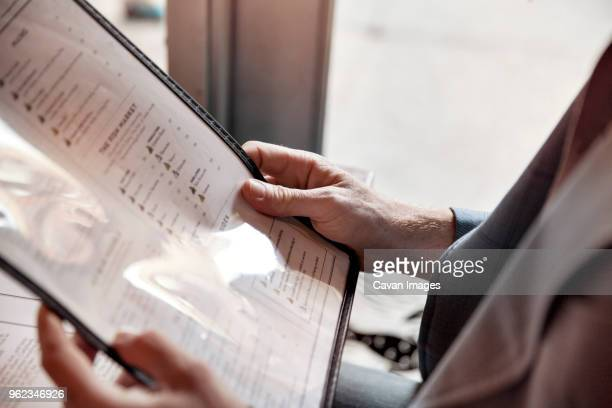 cropped image of man holding menu while sitting in restaurant - menu stock pictures, royalty-free photos & images
