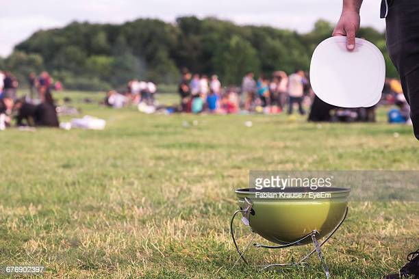 Cropped Image Of Man Holding Plate Over Barbecue Grill On Field