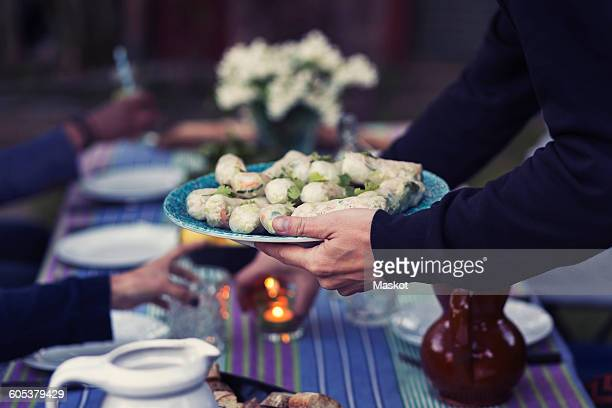 Cropped image of man holding plate with rice paper rolls at outdoor food table during party