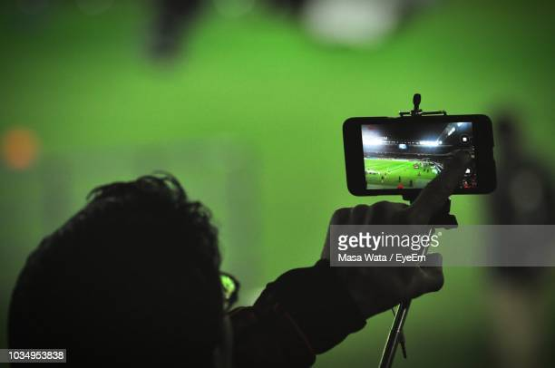 cropped image of man holding selfie stick at football stadium - photographe professionnel photos et images de collection