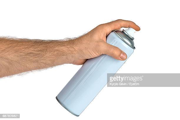 Cropped Image Of Man Holding Spray Bottle Against White Background