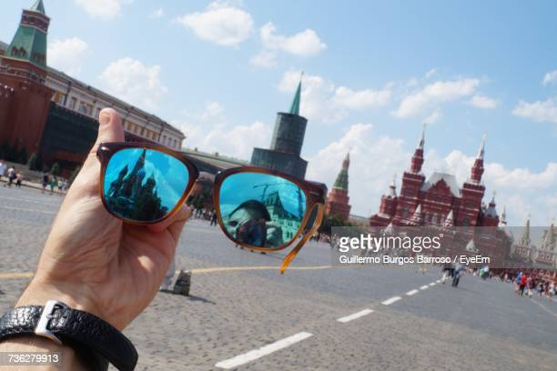 Cropped Image Of Man Holding Sunglasses Against Red Square