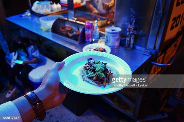 cropped image of man holding taco in plate at food stall - one night stand stock-fotos und bilder